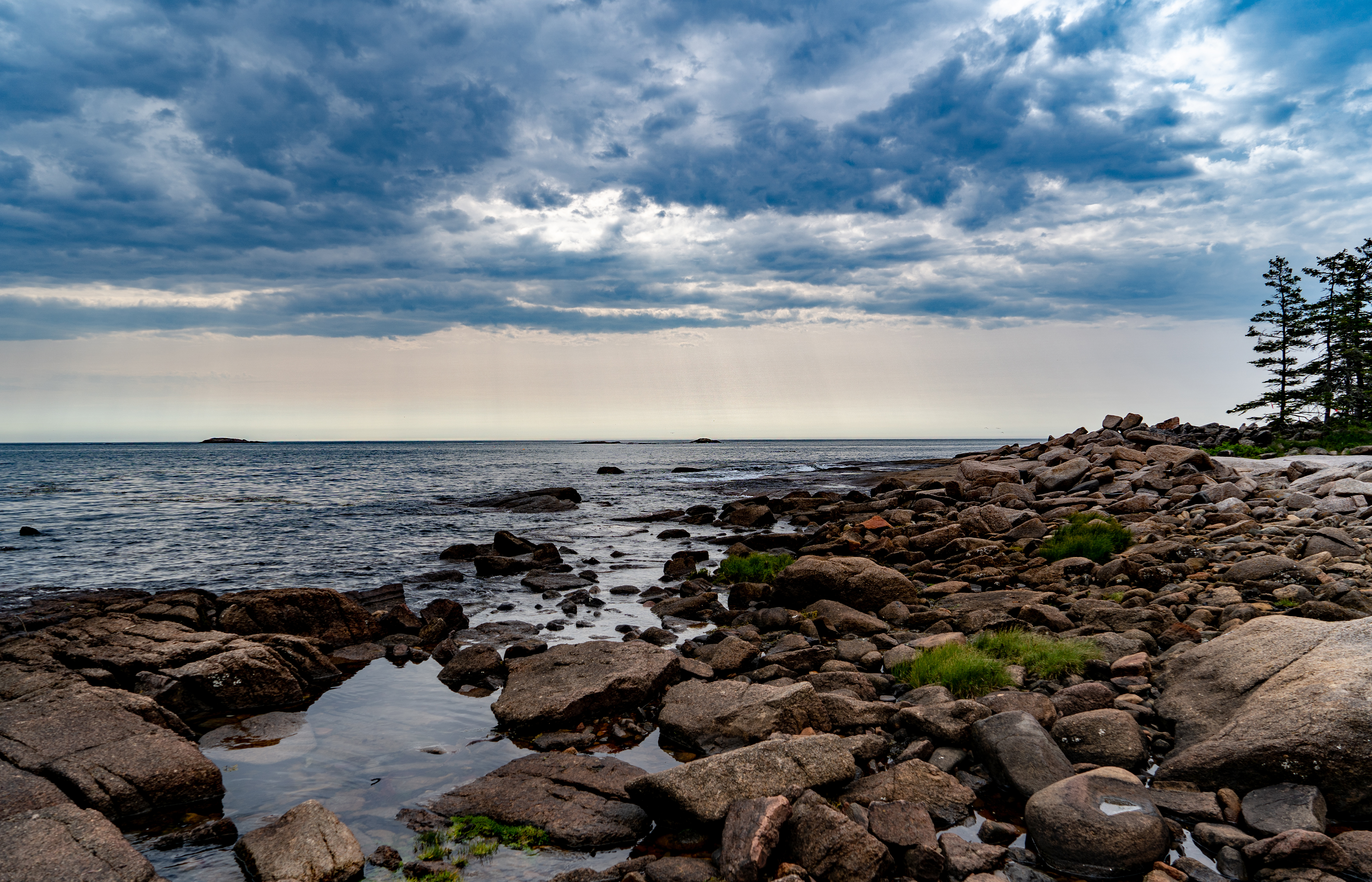 Dramatic clouds hover over a shoreline scene on Great Wass Island