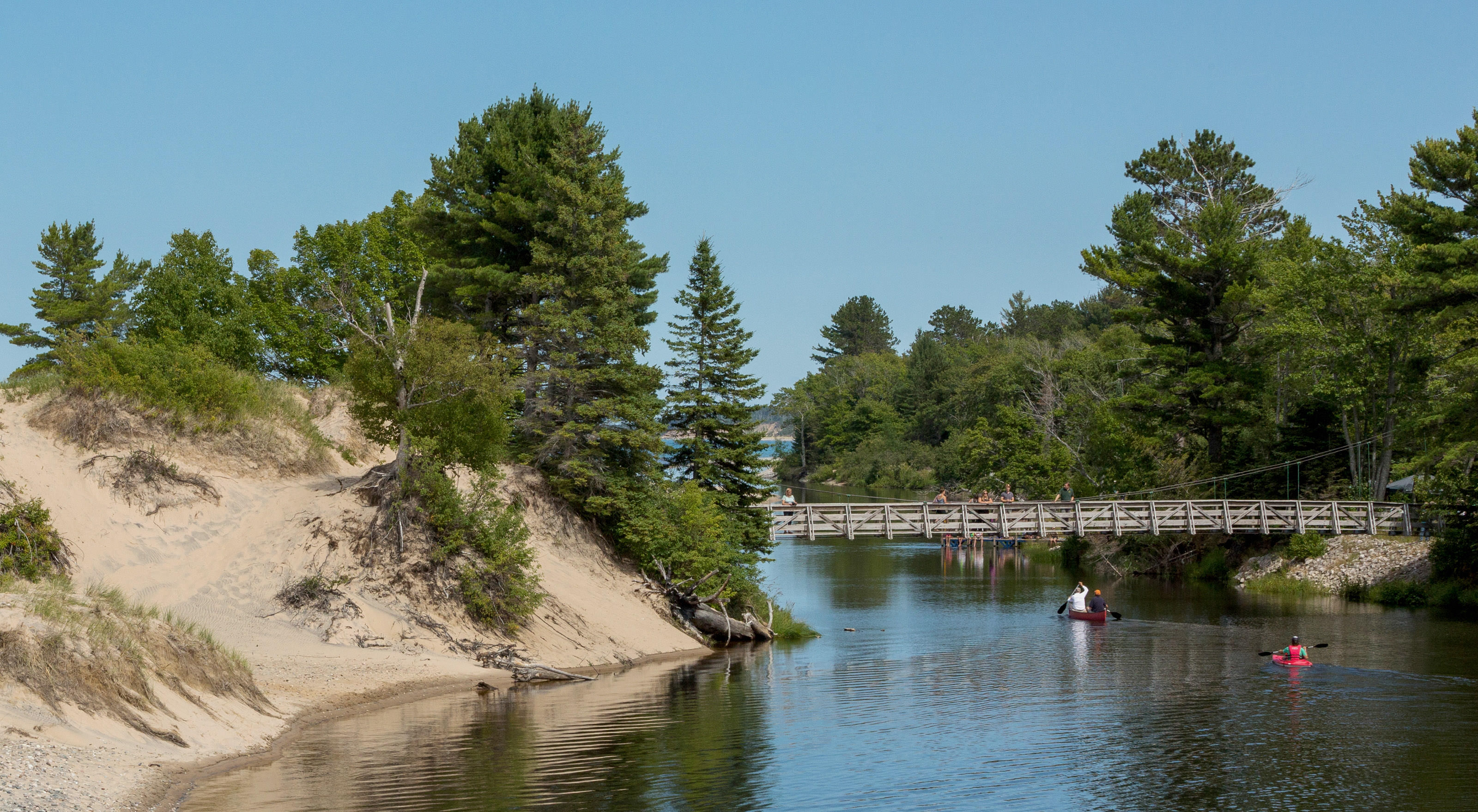 Canoers and kayakers approach the mouth of the Two Hearted River. A sand bank is to the left; a forested bank is the to the right. A footbridge spans above them..