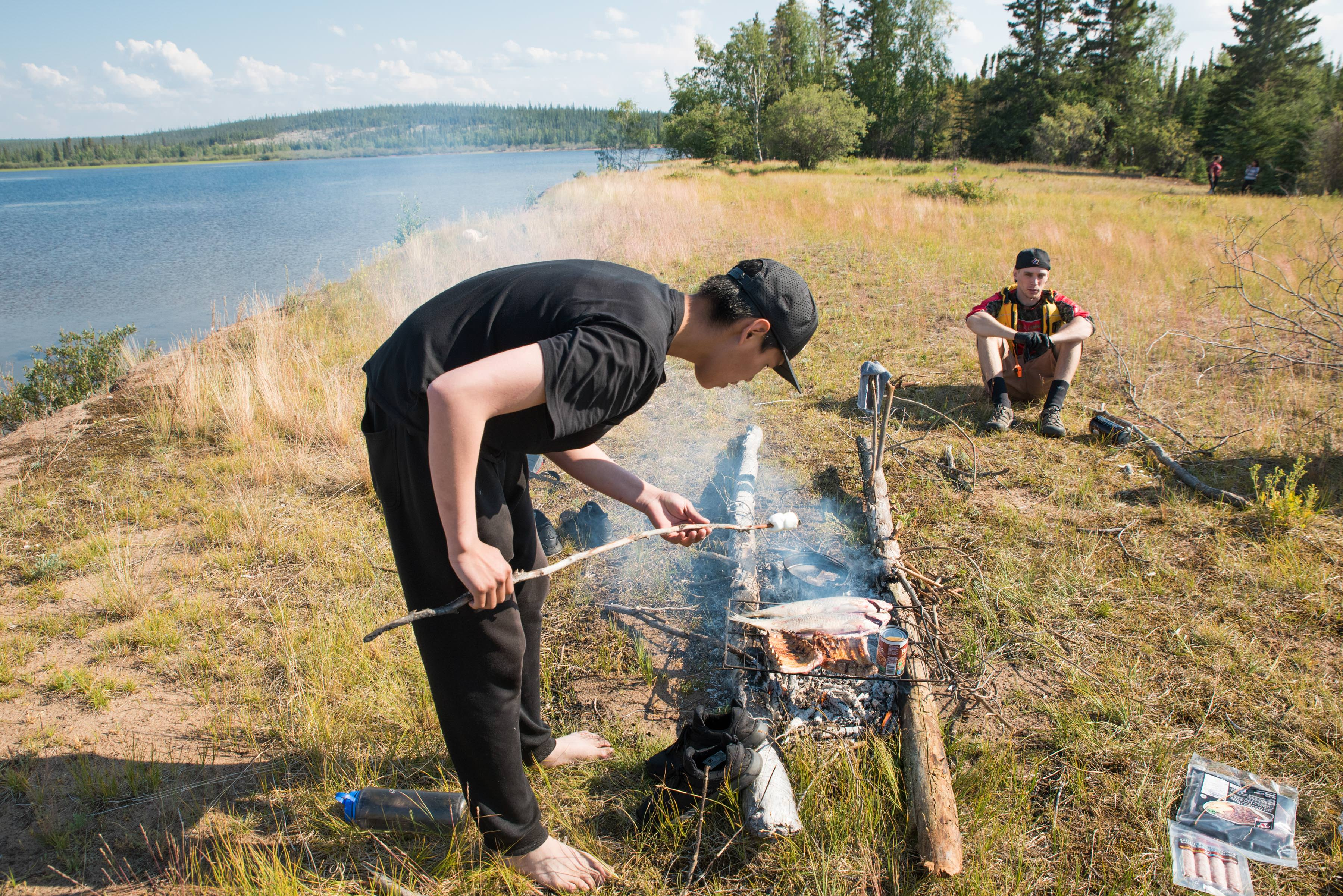 first nation teenage boy roasts marshmallow over fire next to a lake in thaidene nene