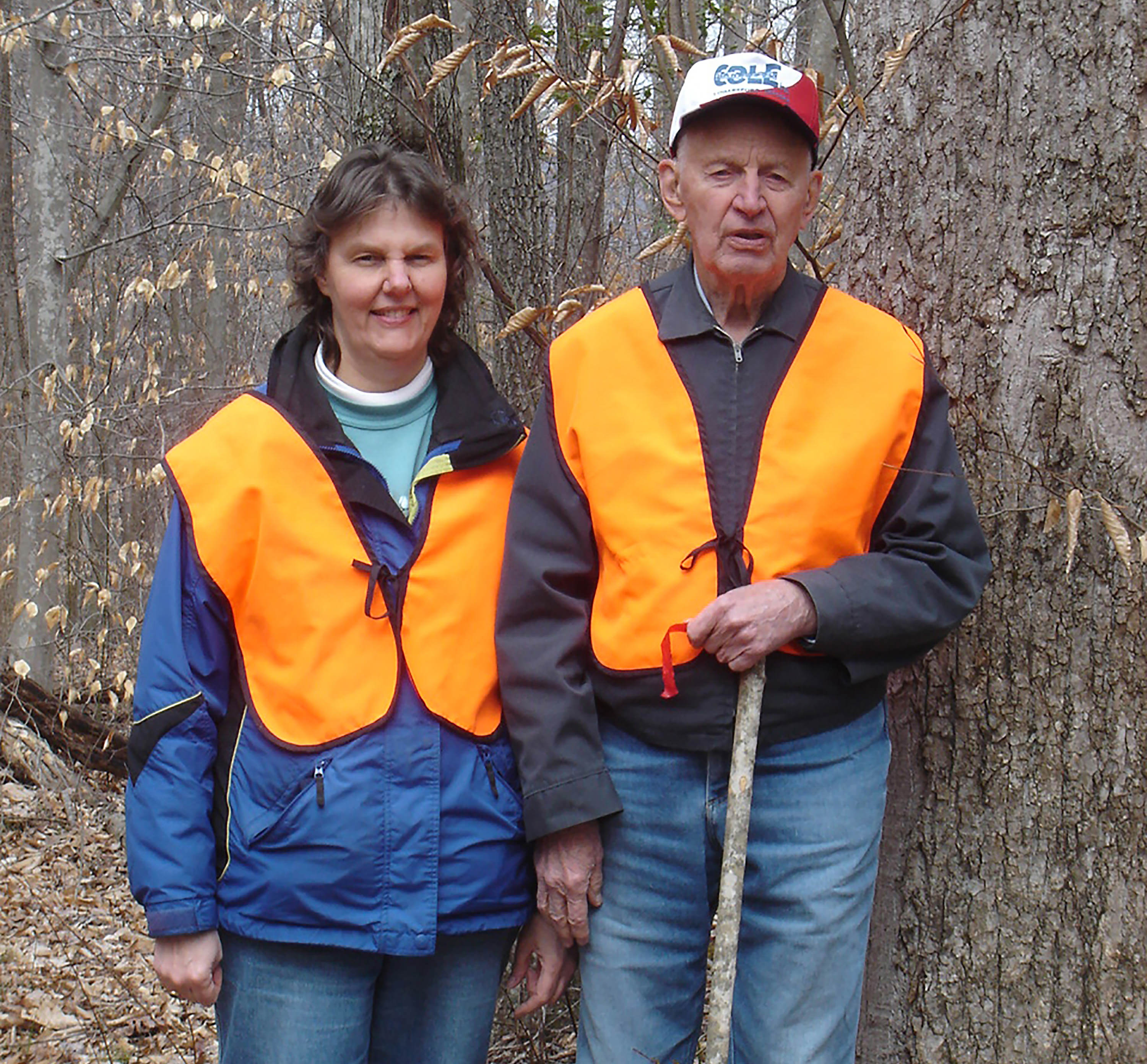 Two people wearing orange vests stand in a forest.