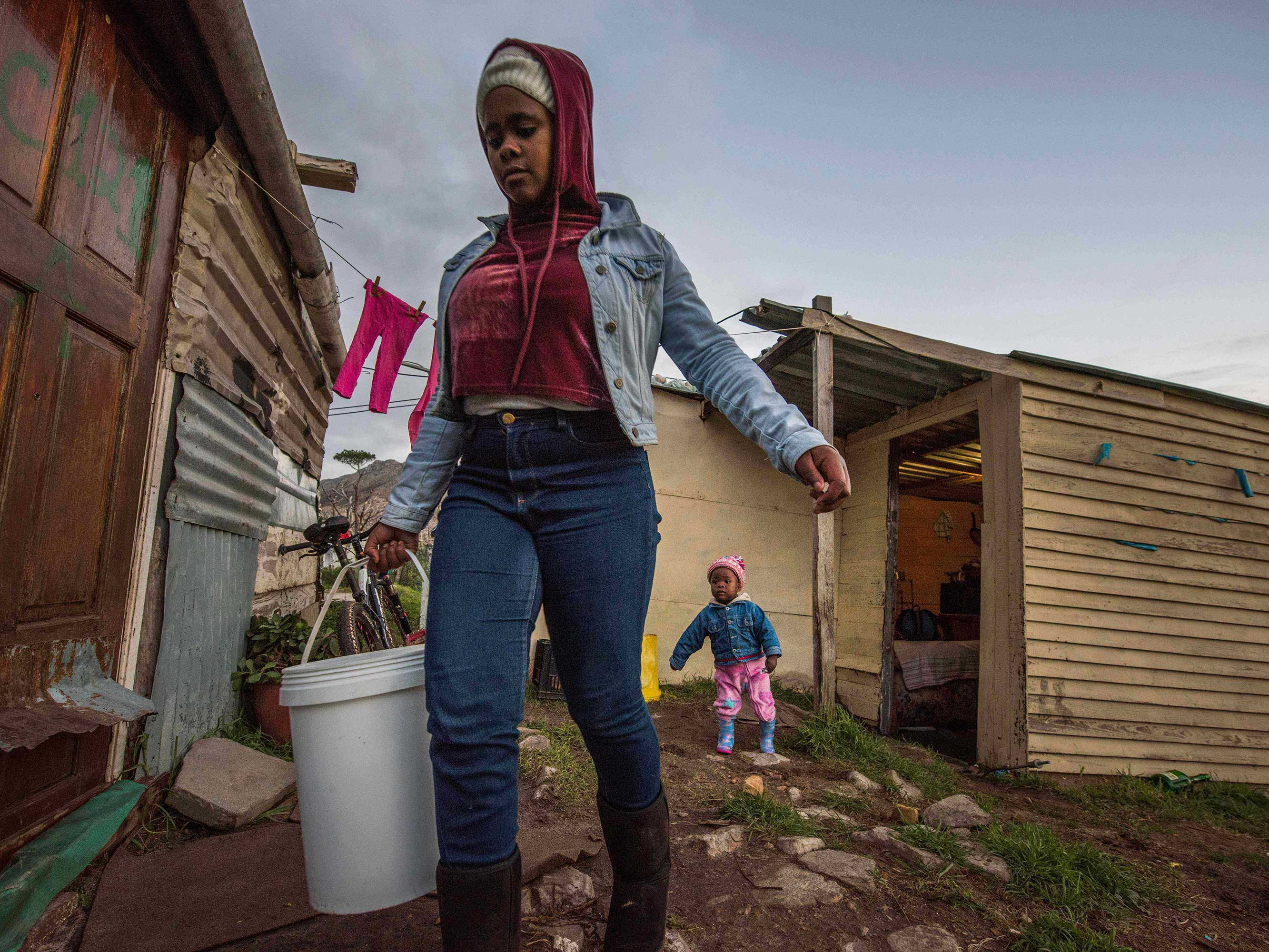woman carries bucket of water in cape town south africa